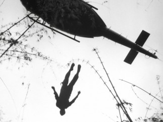 The body of an American paratrooper killed in action in the jungle near the Cambodian border is raised up to an evacuation helicopter, Vietnam 1966